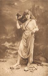 girl in robe stands posed against beach background, she faces forward, looking up to right with jug on her right shoulder