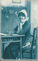 girl in Dutch costume, seated at writing table, facing left, looking front, pen in right hand, left hand to her chin