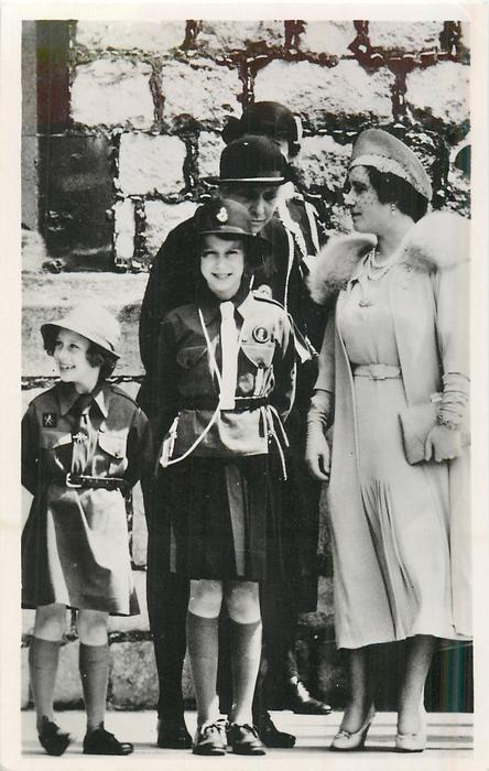 Queen Elizabeth stands right talking to guide leader, both Princesses in guide uniform stand left