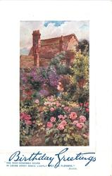 mass of roses & other flowers in foreground, woman bent on path back near large house