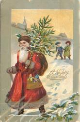 A HAPPY CHRISTMAS Santa with puppets in pocket, green cap & sack of toys walks left with cane