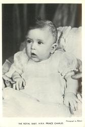 THE ROYAL BABY, H.R.H. PRINCE CHARLES baby sitting in seat with mouth open with adult touching baby's right hand and left arm