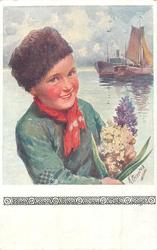 Dutch boy in green shirt, brown hat holds hyacinthe, sea & ships behind