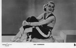 KAY HAMMOND seated on ground with hands together in front of knees, looks back over her shoulder