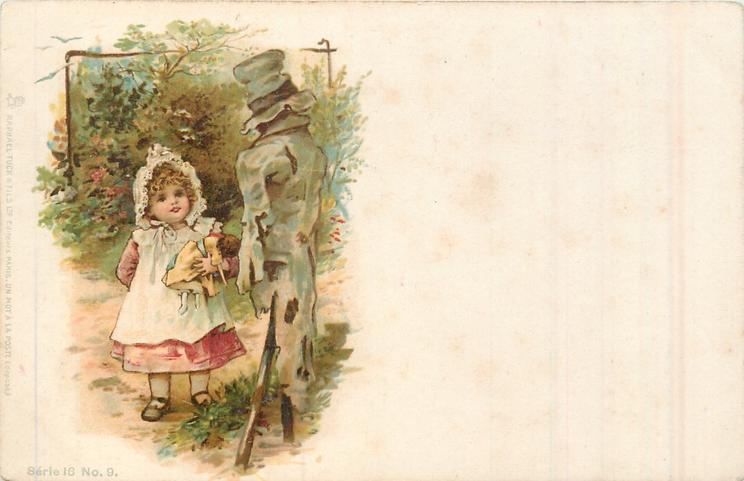 small girl carrying doll stands looking up at scarecrow