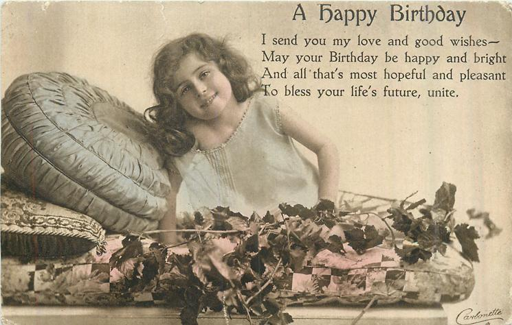 A HAPPY BIRTHDAY flowers in front, she leans forward on pillow