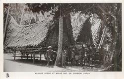 VILLAGE SCENE AT MILNE BAY, S.E. DIVISION, PAPUA eight people standing in front of huts