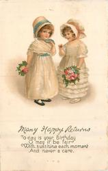 MANY HAPPY RETURNS  two girls with flowers syand facing each other , looking front