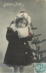 young girl dressed for winter with fur cap, cape & muff, stands facing  front, chun on muff, tree to right