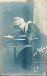 girl in Dutch costume, seated at writing table, pen in right hand, she is bending forward  with head down
