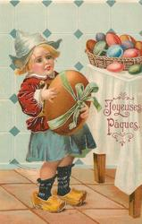 Dutch girl carrying enormouis brown egg looks at basket of Easter eggs on table
