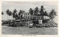 mid-distant  view of  hotel from sea , line of palms across card & in front of hotel