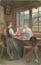 DES LEBENS LENZ  mother holds doll out to child sitting on table