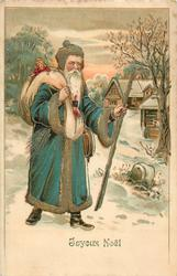 JOYEUX NOEL Santa in green coat with sack over right shoulder, stick in left hand walks front