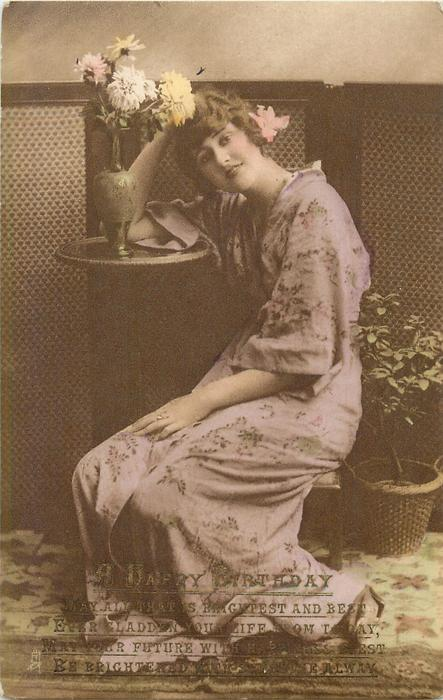 lady in Japanese dress sits on low stool, with left arm on side table, looking front, vase of flowers above left