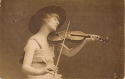 pretty girl in large hat plays violin, facing right & looking down at instrument