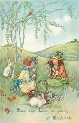 MAY PEACE AND LOVE BE YOURS AT EASTERTIDE 2 girls sit in meadow picking flowers, 2 rabbits