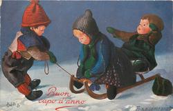 three doll children toboggan on snow