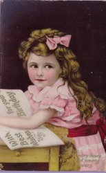 young girl, in pinkdress, sitting at table with book