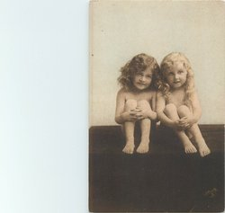 two nude children, one blonde one brunette sitting,side by side with hands on knees, both look front