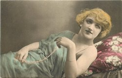 pretty girl ilies on couch, legs to eft, right arm at side left & right hands hold necklace of pearls