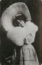 wearing large hat, head tilted to her right