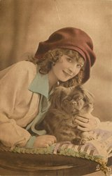 pretty girl in floppy bonnet leans over pekingese dog on cushion on a table, girl faces right but looks forward, has hand under dogs chin